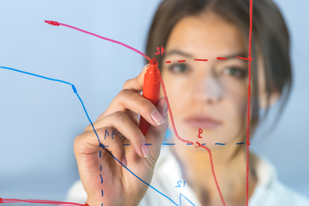 The serious businesswoman draw the graph at the virtual screen