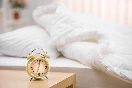 De klassieke klok op de achtergrond van het bed