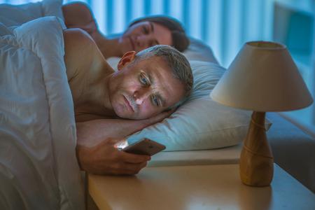 De man met een telefoon lag in de buurt van de slapende vrouw