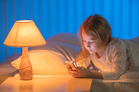 The girl with a phone lay on the bed. Evening night time