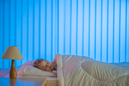 The happy girl sleeping on the bed. Evening night time Stock Photo