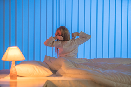 The sleepy girl sitting in the bed. Evening night time Stock Photo