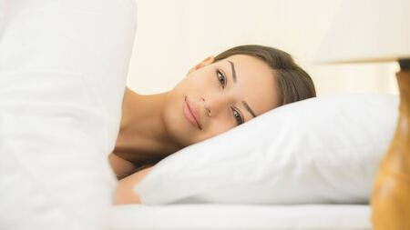 slumber: The cute woman lay on the bed with white linens Stock Photo