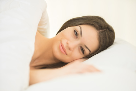 The cute woman lay in the white linens Stock Photo