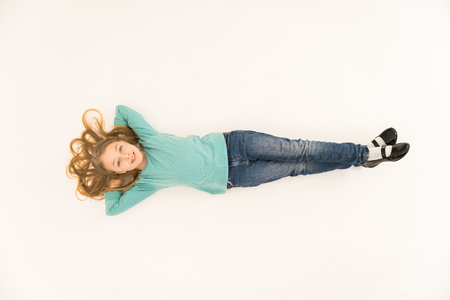 The happy girl lay on the floor. View from above