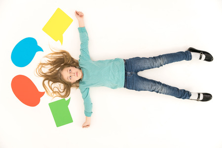 The girl lay on the floor near the dialog signs. View from above Stock Photo
