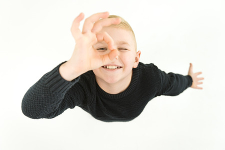 The happy boy gesture to the camera. View from above