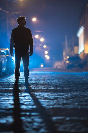 El hombre parado en el camino de la lluvia. Noche por la noche. Toma de lente telefoto