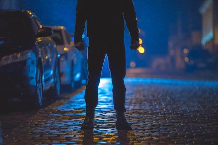 Mężczyzna stoi na mokrej drodze. Wieczorny wieczór. Strzał z teleobiektywem