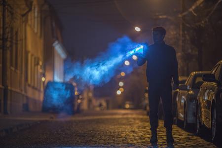 손전등을 가진 남자가 길에 서있다. 저녁 시간