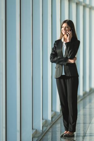 lattice window: The businesswoman phone near the panoramic window