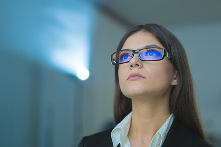 The businesswoman with glasses on the background of projector Stock Photo