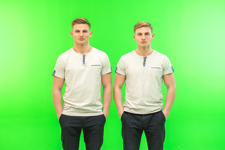 The two handsome twin stand on the green background
