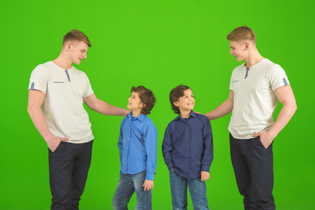 The four brothers stand on the green background Stock Photo
