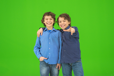 The two little twin gesture on the green background Stock Photo