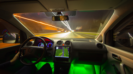 futuristic city: The man drive a car with gps in the night city. Wide angle. Inside view