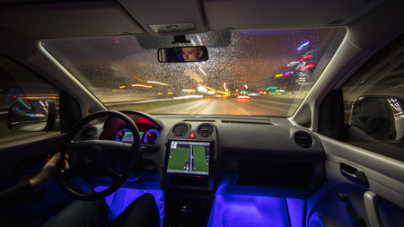 futuristic city: The man drive car in the rainy city. Evening night time