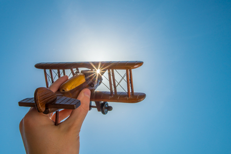 The hand with a toy plane on the background of the clear sky