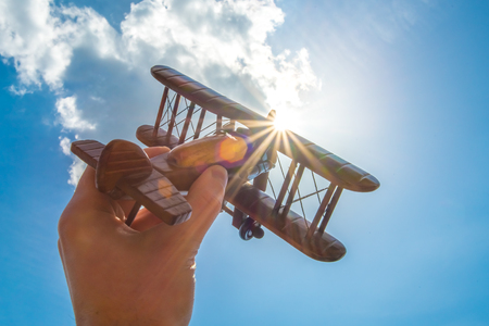 The hand hold a wood plane on the background of the cloud Stock Photo