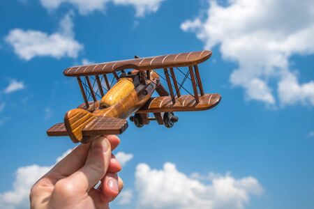 The hand hold a wooden plane on the background of the cloud Stock Photo