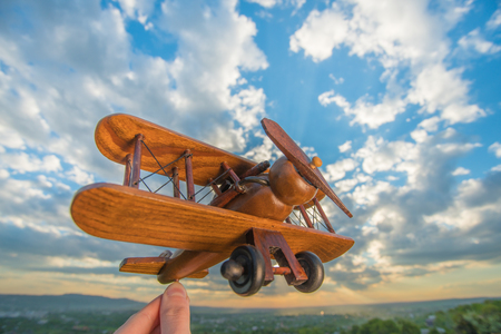The hand hold wooden plane on the background of a blue sky