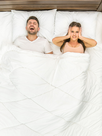 The man snore on the bed. View from above Stock Photo