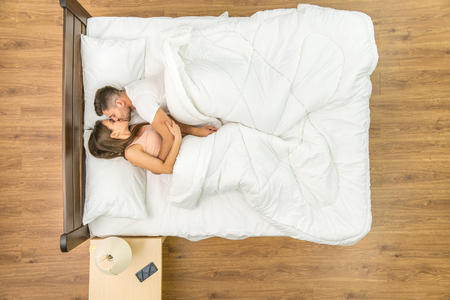 The couple kiss in a bed. View from above