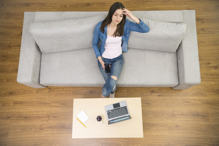upper floor: The woman with a headache sit on the couch. view from above Stock Photo