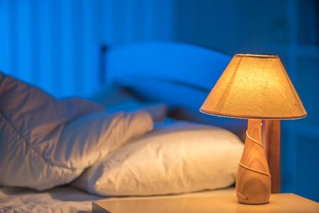 De lamp op de achtergrond van het bed. nachttijd