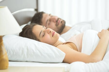 The man and woman sleeping in the comfortable bed