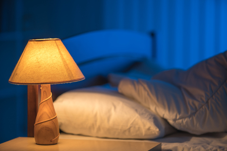 The lamp against the background of the bed. night time Stock Photo