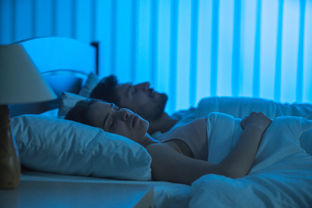 The young couple sleeping on the bed. night time Stock Photo