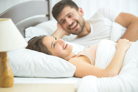 The happy couple lay in the comfortable bed