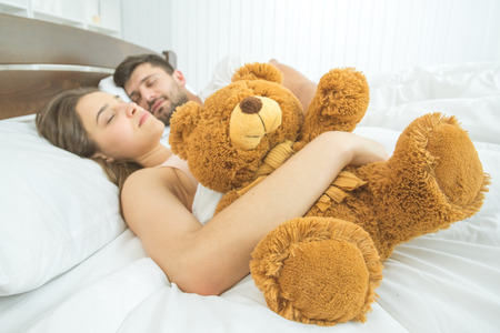 The couple sleeping with a soft toy on the bed Stock Photo