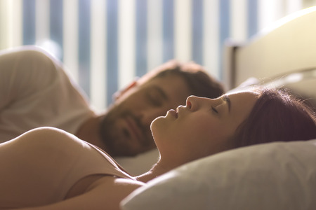 The attractive woman sleeping near the man in the bed