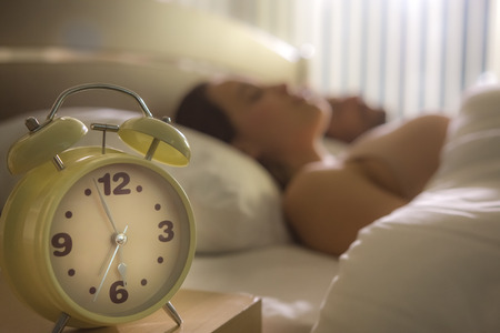 The clock on the background of the couple in the bed Stock Photo
