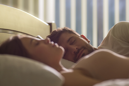 The handsome man sleeping near the woman in the bed Stock Photo