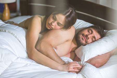 The couple sleeping in the in the bed