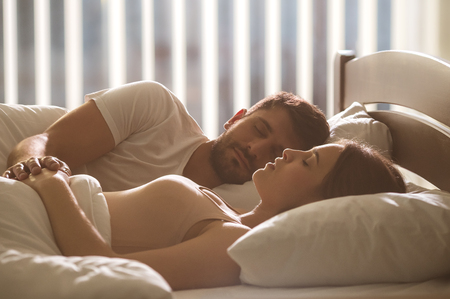The couple sleeping and hold hands in a bed. full grip focus