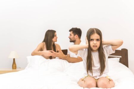 The unhappy girl sit on the background of the arguing parents