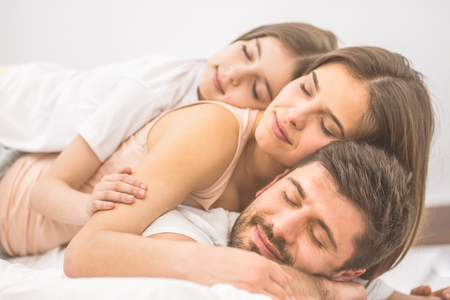 The happy family sleeping on the bed