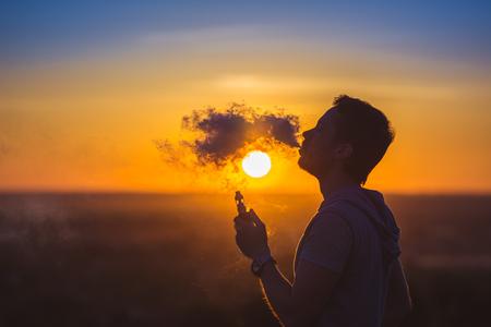 남자는 석양 backround에 전자 담배를 피운다. 스톡 콘텐츠