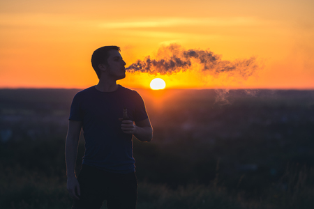 The man smoke an electrical cigarette on the background on the sunrise