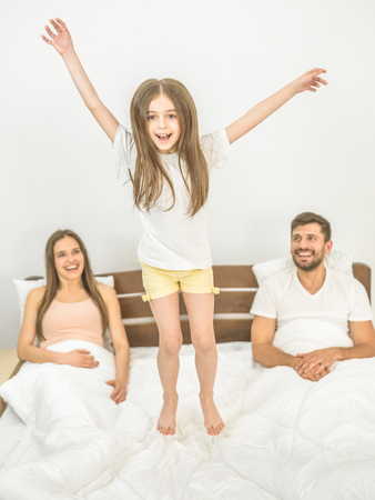 The girl jumping on the bed near parents