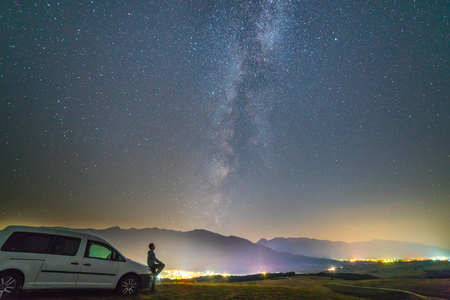 The man stand near the car on the background of the starry sky. night time