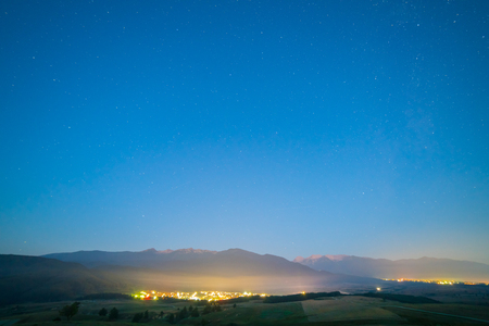 The picturesque city lights on the background of starry sky. evening night time