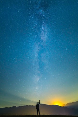 The man stand and gesture on the background of the milky way. night time Stock Photo