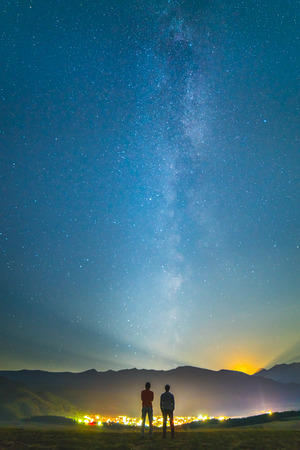 The two friends stand on the background of the starry sky. night time
