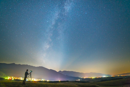 The man with a camera stand on the background of the starry sky. night time