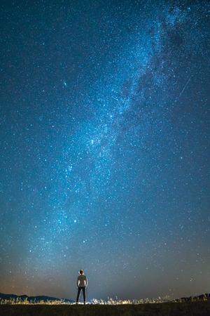 男は星の背景に立っています。夜の時間 写真素材 - 83477211